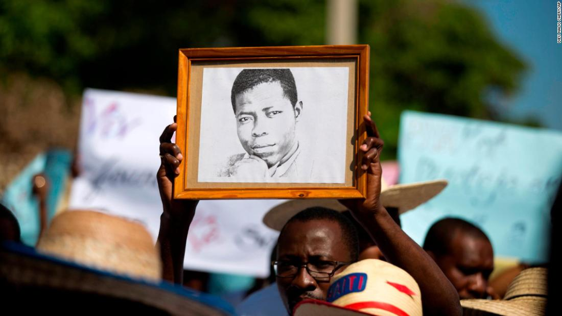 A journalist holds up a framed image of 30-year-old photojournalist Vladimir Legagneur during a march in Port-au-Prince, Haiti, on Wednesday, March 28. Legagneur disappeared in Port-au-Prince on March 14 and has not been heard from since.