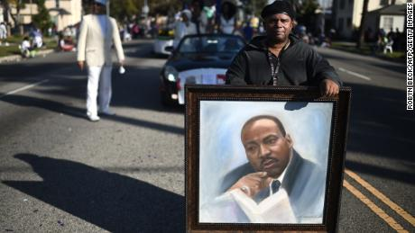 Artist Al Hornsby marches with his painting of  Martin Luther King Jr. in 2015. There are many ways to honor King's memory.