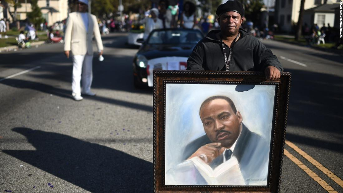 Artist Al Hornsby marches with a portrait of King during the Kingdom Day Parade in Los Angeles in 2015.