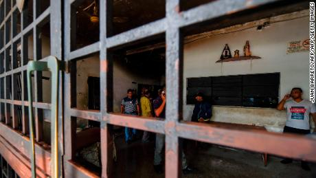 Police agents and journalists talk with surviving prisoners at their cell after holding cells caught fire in Valencia, northern Carabobo state, Venezuela, on March 29, 2018.  A total of 68 people died on Wednesday during an attempted jailbreak in Venezuela after a fire engulfed police holding cells in one of the worst tragedies in years in a notoriously violent and overcrowded prison system. / AFP PHOTO / JUAN BARRETO        (Photo credit should read JUAN BARRETO/AFP/Getty Images)