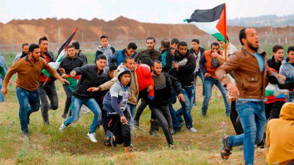 EDITORS NOTE: Graphic content / A picture taken on March 30, 2018 shows a Palestinian youth being carried by other protesters during clashes after a demonstration near the border with Israel east of Jabalia in the Gaza strip commemorating Land Day. Land Day marks the killing of six Arab Israelis during 1976 demonstrations against Israeli confiscations of Arab land. / AFP PHOTO / Mohammed ABED        (Photo credit should read MOHAMMED ABED/AFP/Getty Images)