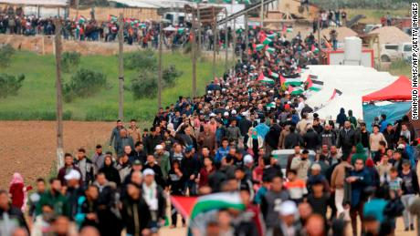 Palestinians march past a tent city erected along the border with Israel.