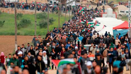 A picture taken on March 30, 2018 shows Palestinians marching past a tent city erected along the border with Israel east of Gaza City in the Gaza strip to commemorate Land Day.