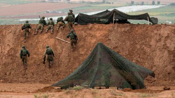 Israeli soldiers take up positions at the border.