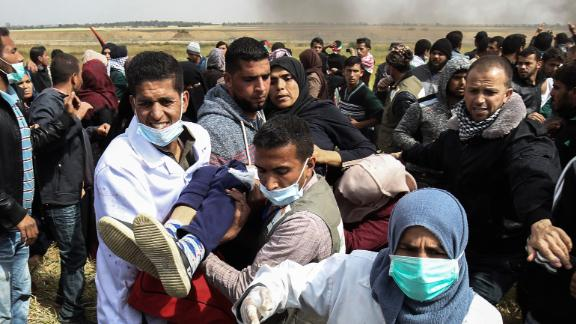 "An injured Palestinian woman is carried by protesters as they run for cover during clashes with Israeli security forces following a demonstration commemorating Land Day near the border with Israel, east of Khan Yunis, in the southern Gaza Strip on March 30, 2018. Clashes erupted as thousands of Gazans marched near the Israeli border in a major protest dubbed ""The Great March of Return"". / AFP PHOTO / SAID KHATIB        (Photo credit should read SAID KHATIB/AFP/Getty Images)"