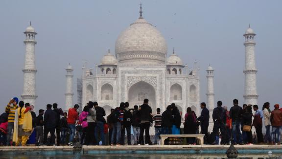 Crowds gather to visit the Taj Mahal in Agra on January 3, 2018.  India is to restrict the number of daily visitors to the Taj Mahal in an effort to preserve the iconic 17th-century monument to love, its biggest tourist draw. Millions of mostly Indian tourists visit the Taj Mahal every year and their numbers are increasing steadily as domestic travel becomes more accessible.  / AFP PHOTO / DOMINIQUE FAGET        (Photo credit should read DOMINIQUE FAGET/AFP/Getty Images)