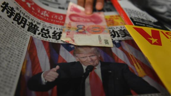 TOPSHOT - A vendor picks up a 100 yuan note above a newspaper featuring a photo of US president-elect Donald Trump, at a news stand in Beijing on November 10, 2016. The world