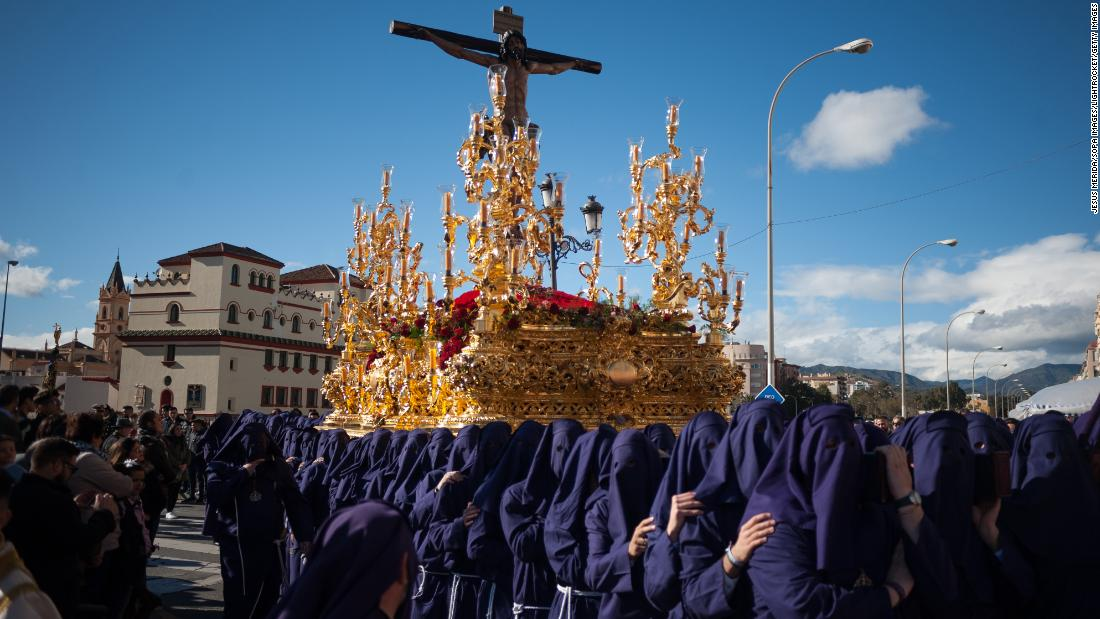 Penitents of the Salud brotherhood carry a statue of Jesus on Sunday, March 25, as people watch the procession during Holy Week in Malaga, Spain. Holy Week in Andalusia is one the most important and famous religious feasts in Spain. Every year, thousands of Christians celebrate the week before Easter by remembering the crucifixion and resurrection of Jesus.