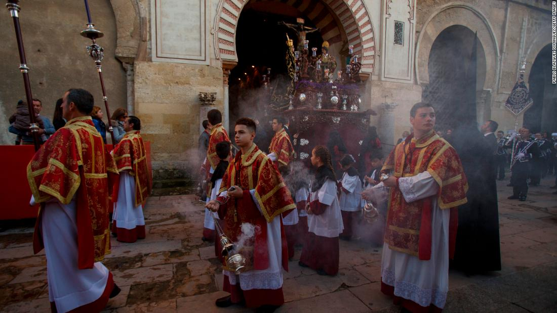 Members of the Las Penas brotherhood take part in a procession at Cordoba's Mosque-Cathedral during Palm Sunday.