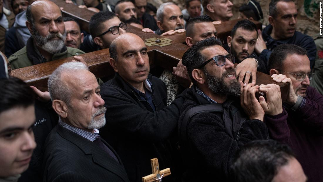 Worshippers carry a wooden cross down to the entrance of the Church of the Holy Sepulcher during the Way of the Cross procession in Jerusalem's Old City on Friday, March 30. Thousands of tourists and pilgrims descended on the holy city to attend activities to mark Christian Holy Week.