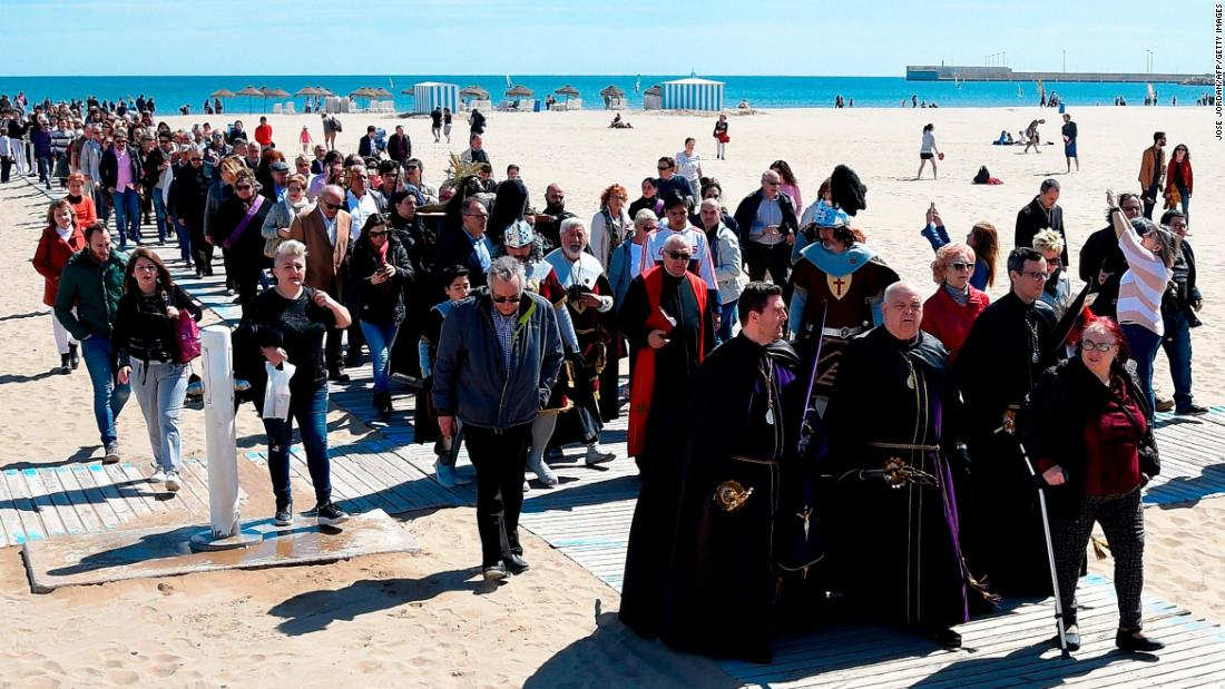 Penitents of the Cristo Salvador y del Amparo brotherhood carry a statue of Jesus on a cross during a Good Friday procession on a beach in Valencia, Spain, on March 30.