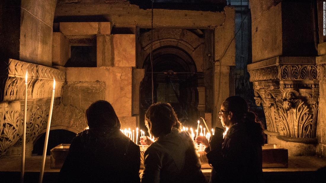 People light candles in the Church of the Holy Sepulcher after the Way of the Cross procession in Jerusalem's Old City on March 30.