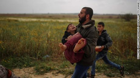 A Palestinian man carries away an injured boy from protests in Gaza on Friday.