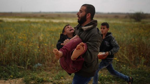 A Palestinian man carries a wounded boy away from protests in Gaza on Friday.