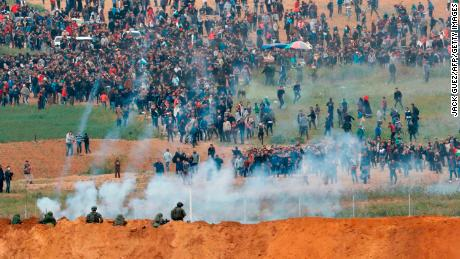 Israeli forces fire tear gas toward Palestinian protesters at the Gaza border fence Friday.