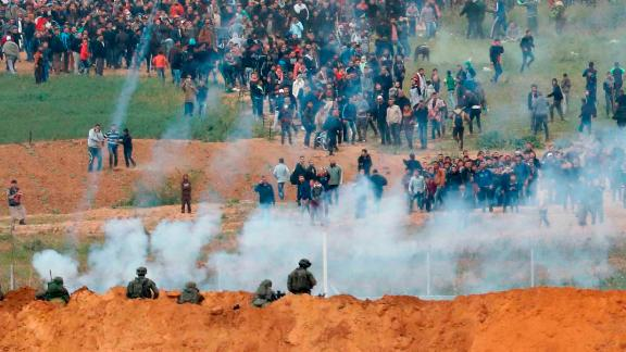 TOPSHOT - A picture taken on March 30, 2018 from the southern Israeli kibbutz of Nahal Oz across the border from the Gaza strip shows tear gas grenades falling during a Palestinian tent city protest commemorating Land Day, with Israeli soldiers seen below in the foreground.Land Day marks the killing of six Arab Israelis during 1976 demonstrations against Israeli confiscations of Arab land. / AFP PHOTO / Jack GUEZ        (Photo credit should read JACK GUEZ/AFP/Getty Images)