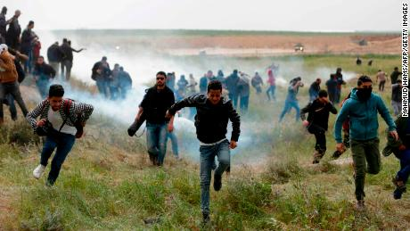 Palestinian protesters flee tear gas during clashes with Israeli forces at the Gaza border on Friday.