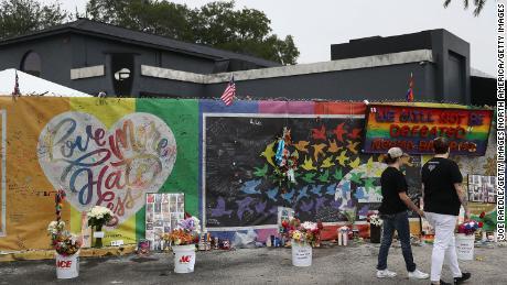 La gente visita un memorial improvisado en Orlando el 12 de junio de 2017, un año después del tiroteo en el club nocturno Pulse.