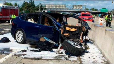 FILE - In this March 23, 2018 file photo provided by KTVU, emergency personnel work a the scene where a Tesla electric SUV crashed into a barrier on U.S. Highway 101 in Mountain View, Calif.  Tesla says, Saturday, March 31,  the vehicle in a fatal crash last week in California was operating on Autopilot, the latest accident to involve self-driving technology. The automaker says the driver, who was killed in the accident, did not have his hands on the steering wheel for six seconds before the crash. Tesla says its Autopilot feature, which can keep speed, change lanes and self-park, requires drivers to keep their eyes on the road and hands on the wheel to take control of the vehicle to avoid accidents. (KTVU via AP)