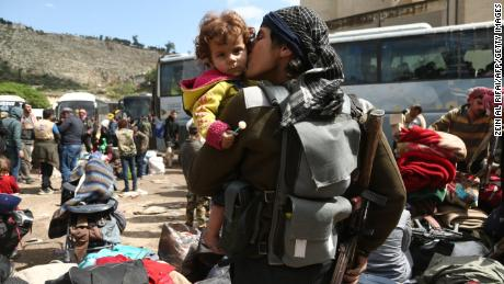 A rebel fighter from Eastern Ghouta kisses a child after arriving in Qalaat al-Madiq on Friday, as part of the ongoing evacuation deals.