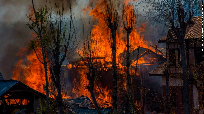 Homes where militants took refuge during a gun battle with Indian armed forces are engulfed in flames on April 1, 2018, in Indian-administered Kashmir.