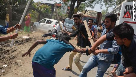 A protester is beaten by students during protests in India's Uttar Pradesh state on Monday.