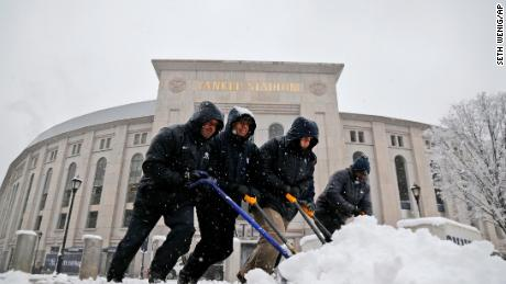 Men shovel snow from the sidewalks in front of Yankee Stadium on Monday.