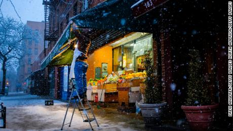 A worker adjusts the awning to protect fruits and vegetables sitting outside at his produce store on Atlantic Avenue in Brooklyn on Monday.