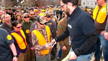Rob Curtis hands out 30-round magazines at a protest outside the Vermont Statehouse.