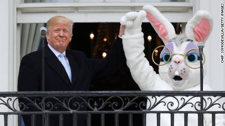 U.S. President Donald Trump (L) lifts the hand of a person in an Easter Bunny costume on the Truman Balcony during the 140th annual Easter Egg Roll on the South Lawn of the White House April 2, 2018 in Washington, DC. The White House said they are expecting 30,000 children and adults to participate in the annual tradition of rolling colored eggs down the White House lawn that was started by President Rutherford B. Hayes in 1878.  (Photo by Chip Somodevilla/Getty Images)