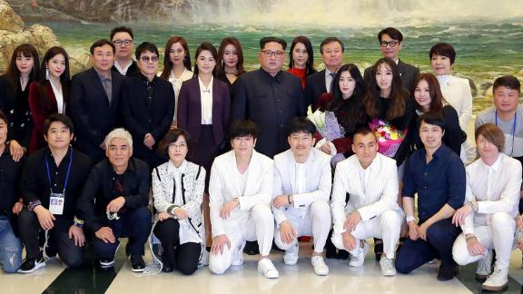 This April 1, 2018 picture released from North Korea's official Korean Central News Agency (KCNA) on April 2, 2018 shows North Korean leader Kim Jong-Un  and his wife Ri Sol-Ju  posing with South Korean musicians after a rare concert.