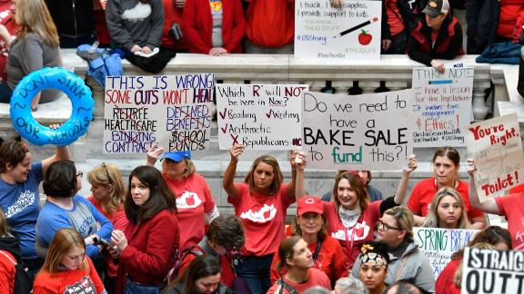 Teachers from across Kentucky hold up signs as they fill the state Capitol to rally for increased funding and to protest last minute changes to their state funded pension system, Monday, April 2, 2018, in Frankfort, Ky. (AP Photo/Timothy D. Easley)