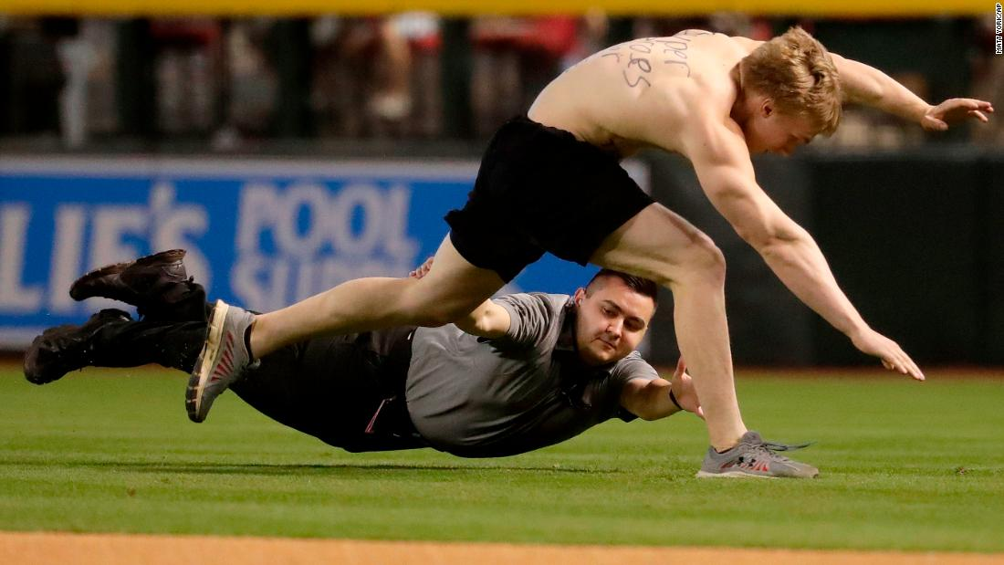 A fan is tackled by security after running onto the field during a Major League Baseball game in Phoenix on Thursday, March 29.