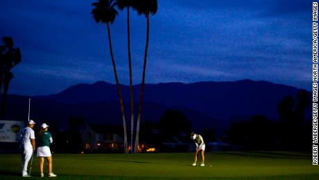 Pernilla Lindberg putts during Sunday's playoff as darkness falls.