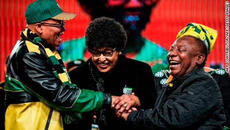 Winnie Mandela (C) holds the hands of then-President Jacob Zuma (L) and future President Cyril Ramaphosa at the ANC conference in June 2017.