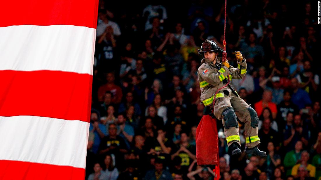 A firefighter repels to the court during the National Anthem.