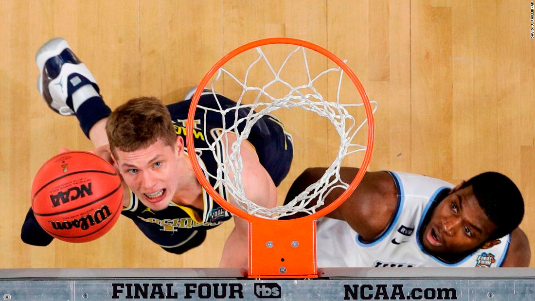 Michigan's Moritz Wagner goes for a layup next to Paschall.