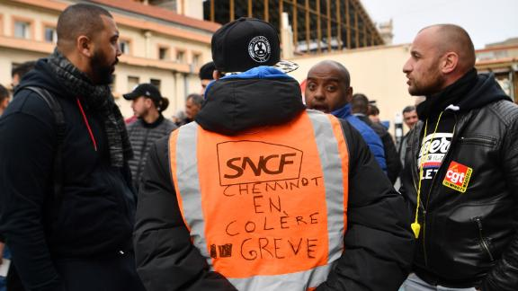 """A man wearing a jacket reading """"angry railway worker on strike"""" at a Marseille train station on Tuesday."""
