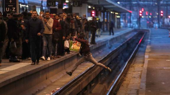 A passenger crosses the tracks at Gare de Lyon train station in Paris on Tuesday.