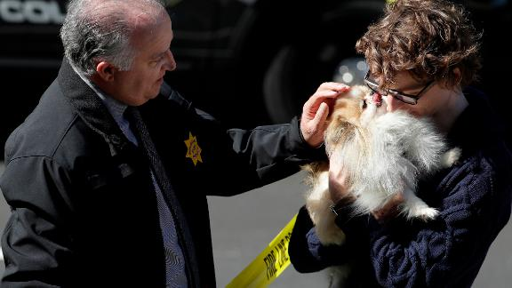 Burlingame Police Chief Eric Wollman hands a dog named Kimba to a man who didn