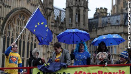 Anti-Brexit demonstrators wave European Union flags from the top deck of a bus parked outside the Houses of Parliament in London on March 29, 2018. British Prime Minister Theresa May kick-started divorce proceedings one year ago, and March 29, 2019, has since been set as the date the UK will leave the bloc. / AFP PHOTO / DANIEL LEAL-OLIVAS        (Photo credit should read DANIEL LEAL-OLIVAS/AFP/Getty Images)