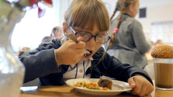 Children enjoy lunch, including meat and vegetables, at the Kolno village school in Belarus, a landlocked country in Eastern Europe. Experts say that eating well-balanced meals can benefit a child