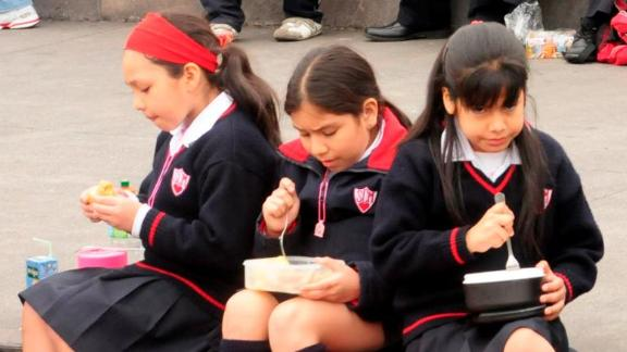 Middle school students enjoy lunch outdoors in Lima, Peru. Many children pack lunches brought from home that include juice boxes, fruit and traditional dishes.