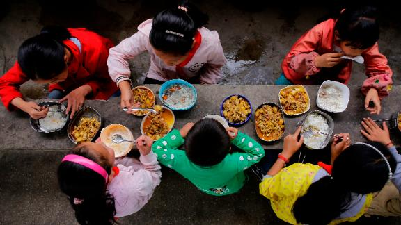 Students eat a free lunch, consisting of rice and traditional dishes, at Yuanbao school in Guizhou, a mountainous province in southwest  China. Free lunch has been sponsored by the central government since 2011 to improve students