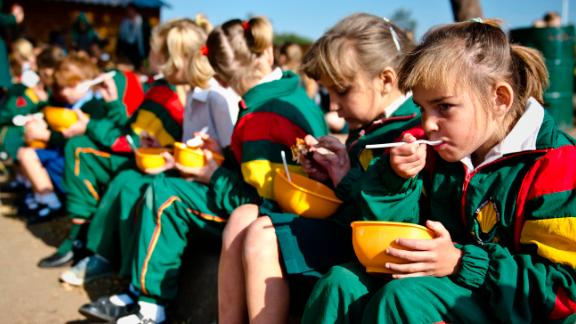 Students eat lunch at David Brink Primary School in Rustenburg, South Africa, where the number of students benefiting from the school