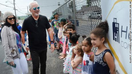 Chicago Cubs Manager Joe Maddon and his wife Jaye are all smiles as they see the new playground at the Hazleton One Community Center and the day care children waiting for it to open in Hazleton, Pa., on Thursday, June 15, 2017. (Ellen F. O'Connell/Hazleton Standard-Speaker via AP)