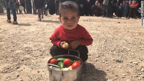 A boy from Eastern Ghouta shows his family's daily pot of food.