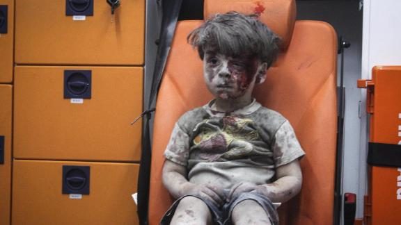 This still image, taken from a video posted by the Aleppo Media Center, shows a young boy in an ambulance after an airstrike in Aleppo, Syria, on August 17, 2016. It took nearly an hour to dig the boy, identified as Omran Daqneesh, out from the rubble, an activist told CNN. The airstrike destroyed his home, where he lived with his parents and two siblings. Director of the Aleppo Media Center Yousef Saddiq said Omran