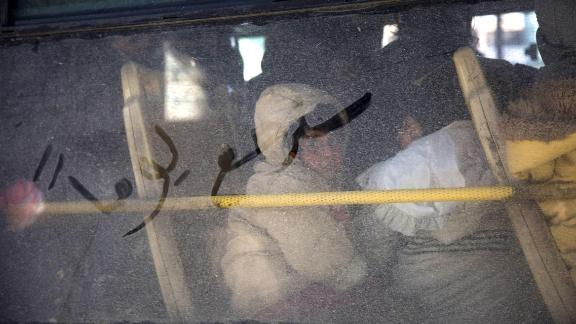 """Arabic writing that reads """"some day we will return"""" is seen on a bus window as civilians evacuate Aleppo on December 15, 2016. The evacuations began under a new ceasefire between rebels and pro-government forces."""