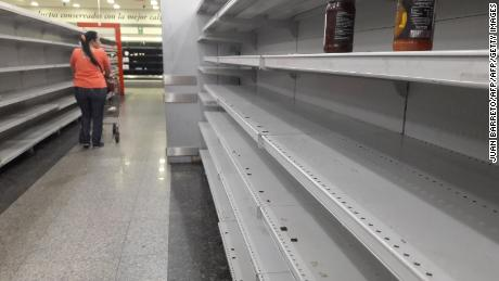 "A woman walks between the empty shelves of a supermarket in Caracas on January 11, 2018.  Colombian President Juan Manuel Santos, on Thursday called his Venezuelan counterpart Nicolas Maduro to accept international aid to help Venezuelan people to stop ""suffering hunger and lack of medicines"". / AFP PHOTO / JUAN BARRETO        (Photo credit should read JUAN BARRETO/AFP/Getty Images)"